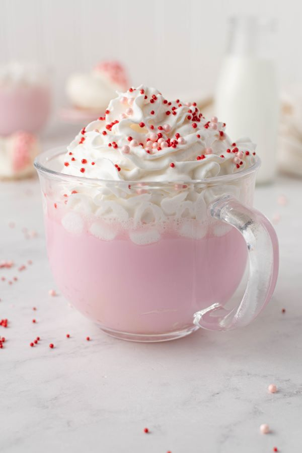 Side view of the final strawberry hot chocolate with whipped cream and red and pink sprinkles.