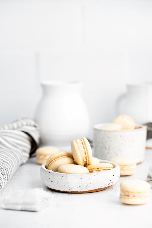 Earl Grey Tea Macarons in a white bowl with black specks.
