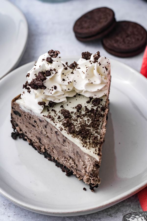A slice of oreo cheesecake on a white plate with a pink linen and oreos in the background