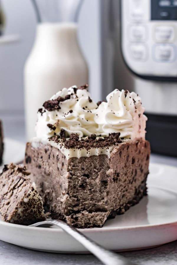 Front view of a slice of oreo cheesecake with a bite removed on a white plate with a silver fork. Milk and Instant Pot in the background.