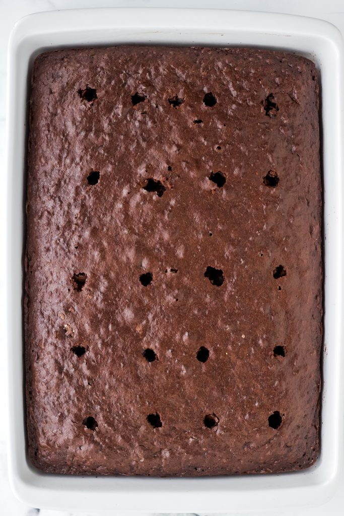Baked chocolate cake with holes poked one inch apart across the top