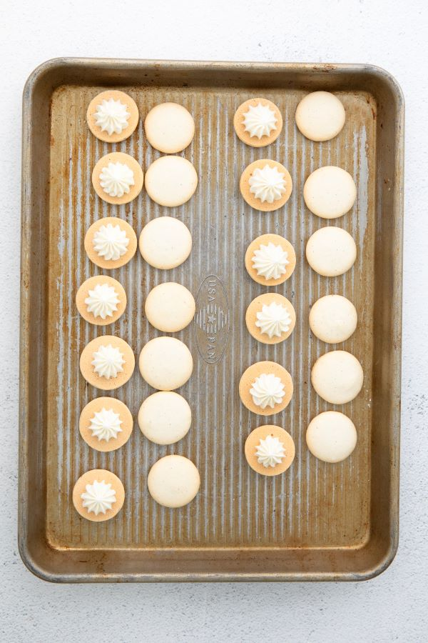 Macarons being assembled on a cookie sheet.