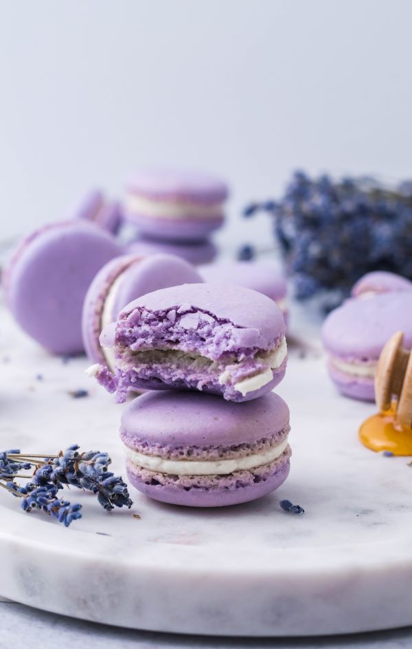 Several Lavender Macarons on a marble slab. One has a bite taken out of it