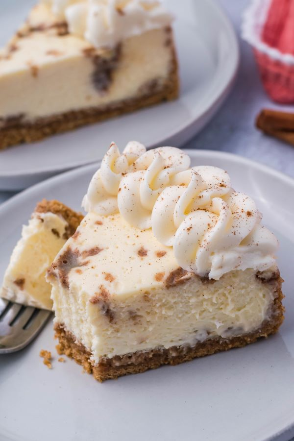 cinnamon roll cheesecake on a white plate with a bite on a fork.