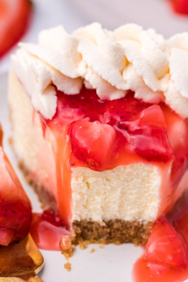 Close up shot of a slice of Strawberry cheesecake with a bite removed.