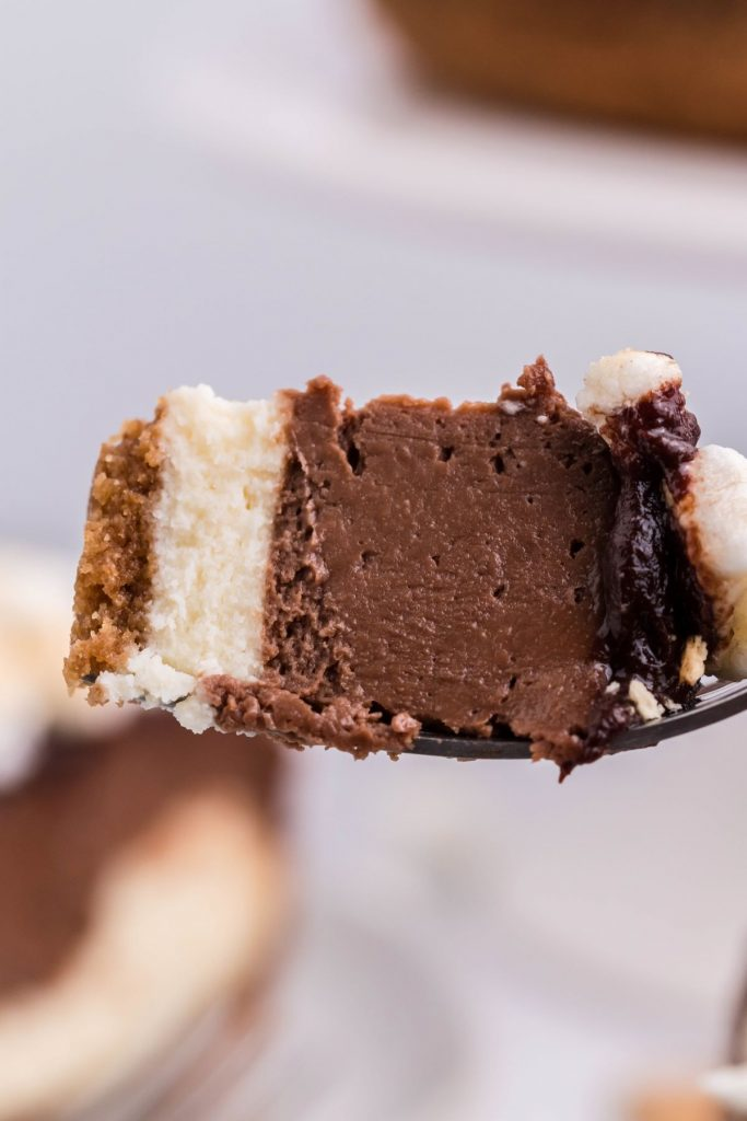 A piece of air fryer s'mores cheesecake on a fork showing the different layers.