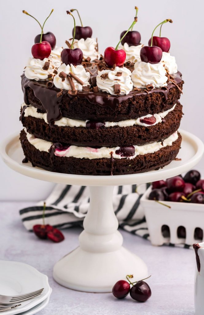 Front view of the whole German black forest cake on a white cake stand with fresh cherries in the background. Black and white stripped linen.