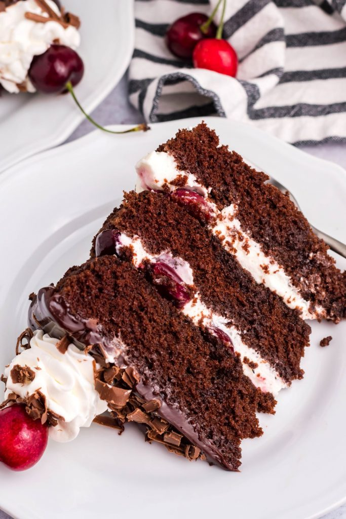 A slice of German Black Forest Cake on a white plate with a silver fork. Black and white stripped linen in the background with fresh cherries.